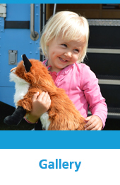 Photo of a little girl holding a fox puppet with the text Gallery