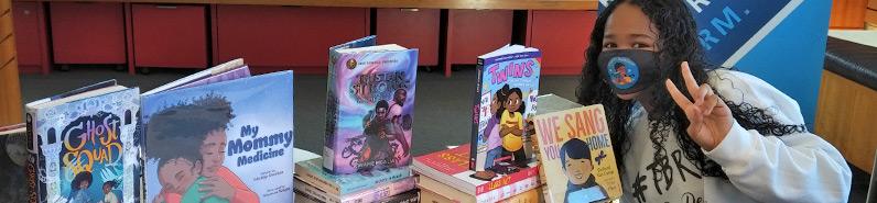 Ainara Alleyne seated beside a pile of HPL books.