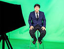 man sitting on stool in front of green screen with fill light to the side