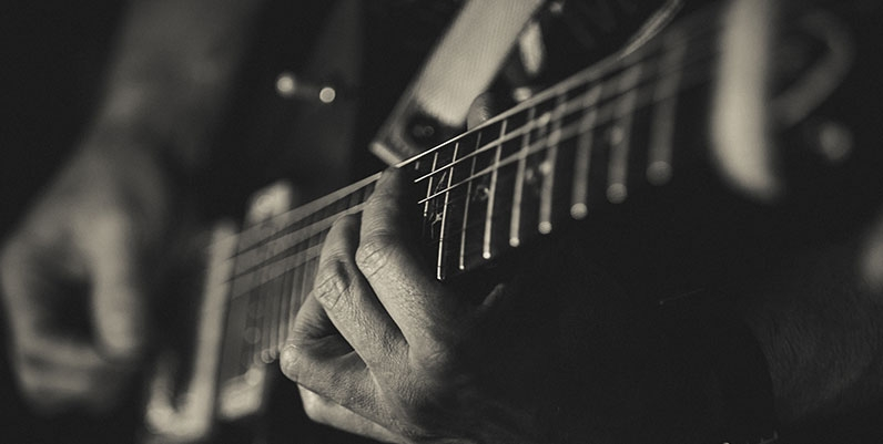black and white photo of a person playing an acoustic guitar