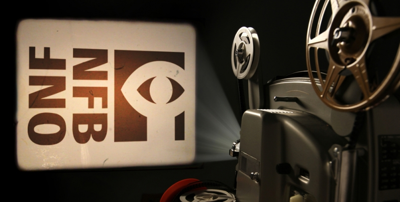 Photo of a film projector projecting the National Film Board logo onto a wall