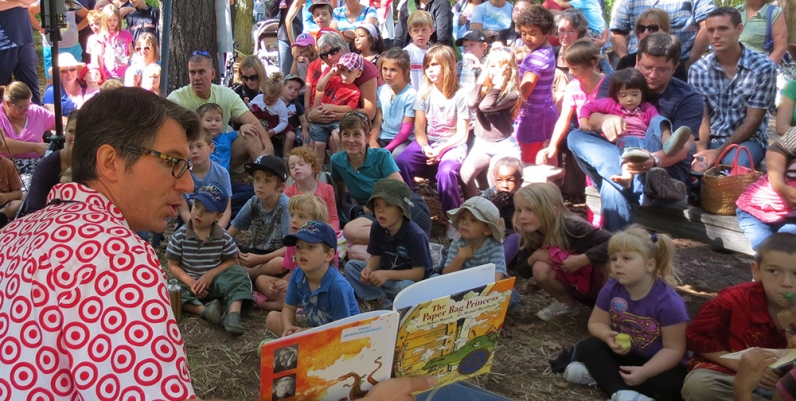 Man reading a story to a group of children at the Telling Tales Festival