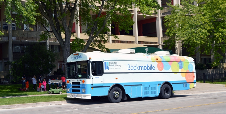 Photo of the HPL Bookmobile parked on the street in front of an apartment building