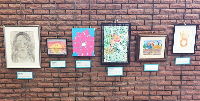 different paintings and artworks hung on a brick wall