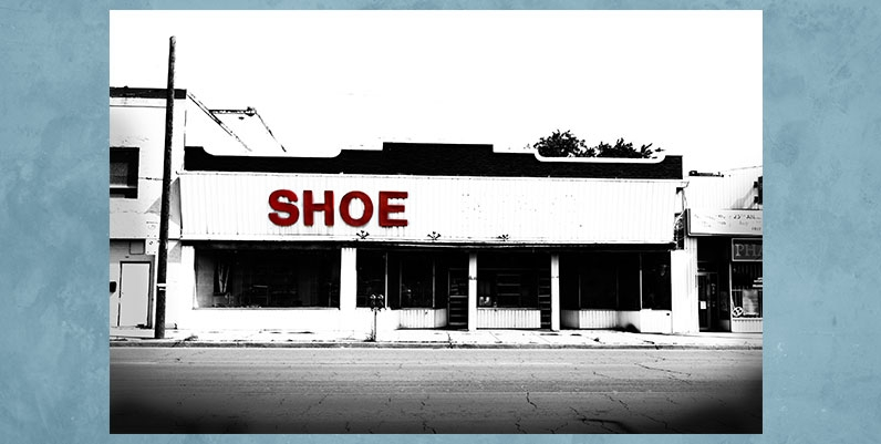 black and white photo of a closed shoe store