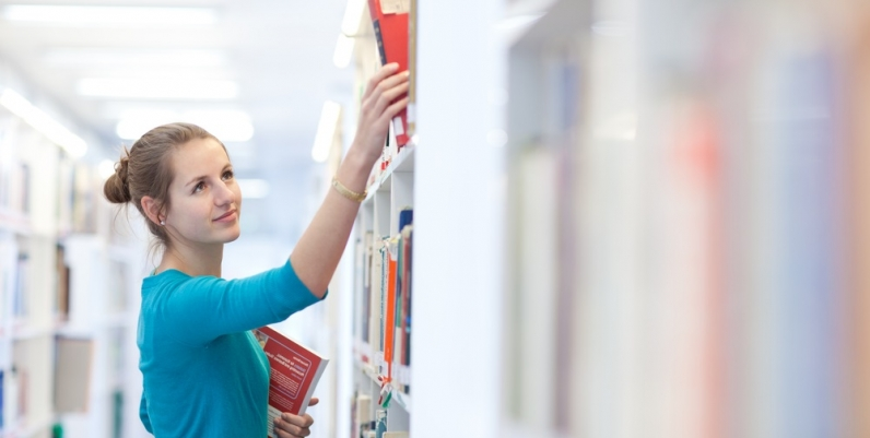 Woman choosing book from shelf