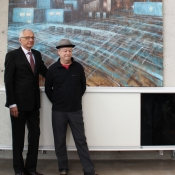 two men in front of a painting