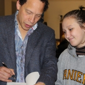 an author signing a book for a teen girl