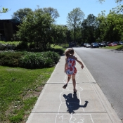 Young girl plays hopscotch on a chalk drawn board on the sidewalk