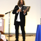 male standing on a stage and reading from a book