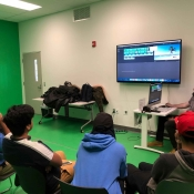 An image of students sitting in the green room at Central Library learning about the software and green screens
