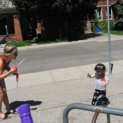 Woman blows bubbles for a young child outside