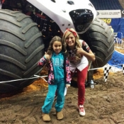 a girl and a woman posing for a photo in front of a monster truck