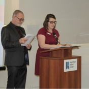 a photo of a male and female hosting an event behind a podium