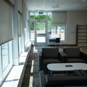 Tables and chairs inside the new greensville branch near a window