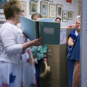 An HPL staff member conducting a tour of the local history archive's and discussing a book from the collection