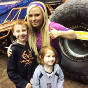 two boys and a woman posing for photos in front of a monster truck