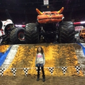 girl posing in front of a monster truck