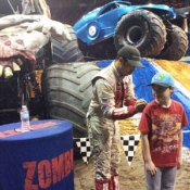 a boy getting an autograph from a monster truck driver