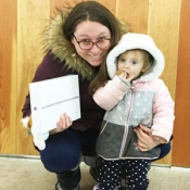 woman and toddler holding ipad and library card