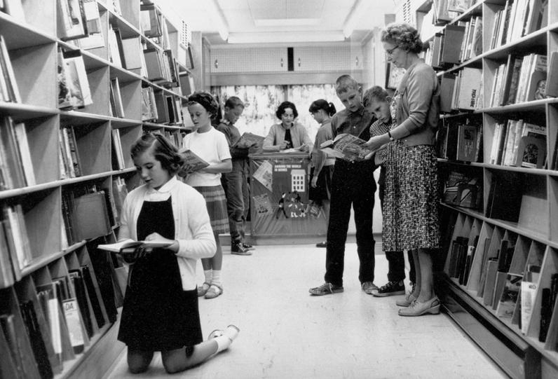 Archival photo of children inside the Bookmobile circa 1950s