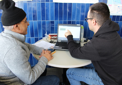 Two individuals sat at a table with a laptop computer partaking in tutoring