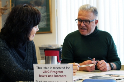 Man and women sitting together at a table with a sign that reads This table is reserved for LINC tutors and learners.