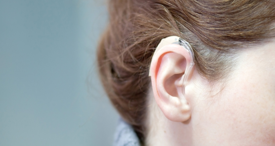 Photo of a woman's ear wearing a hearing aid