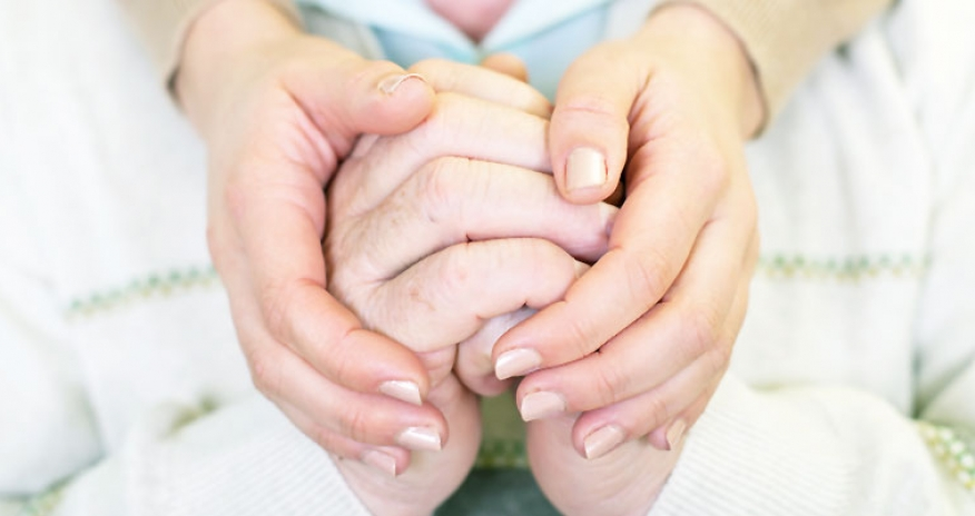 a close up of elderly hands and caregiver holding hands