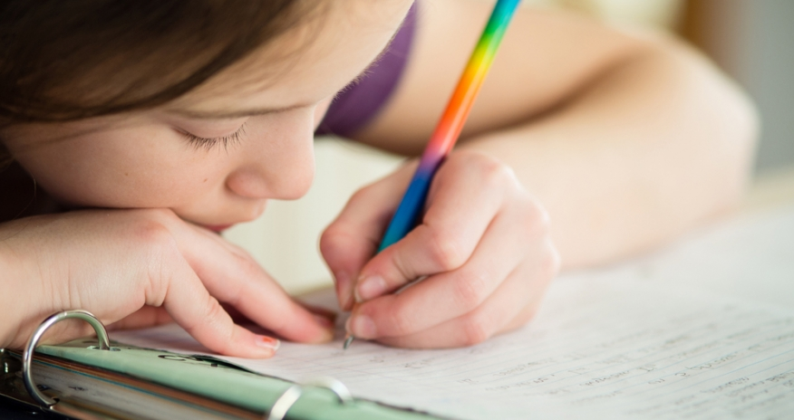 Closeup of a young girl writing in a notebook