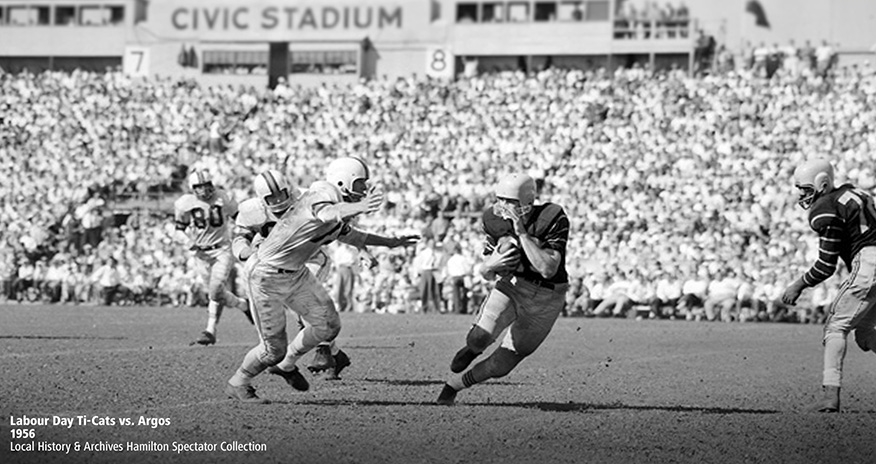 Black and white image of a football game with the text Labour Day Ti-Cats vs. Argos, 1956, Local History and Archives Hamilton Spectator Collection