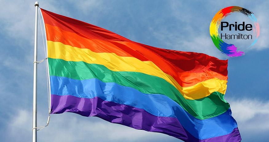 The pride flag with the Pride Hamilton logo in the upper right corner