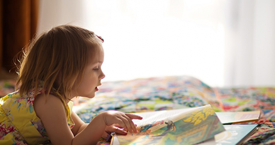 a female toddler reading a book