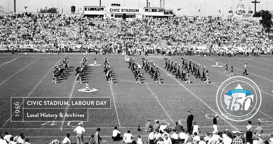 black and white photo of a parade on a football field