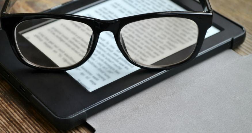 Reading glasses resting on an eReader