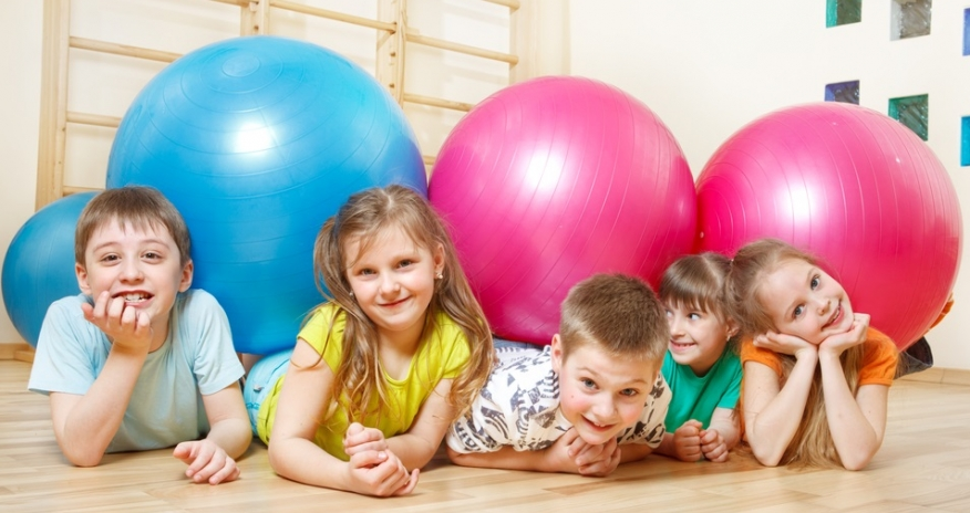 A group of children playing with exercise balls