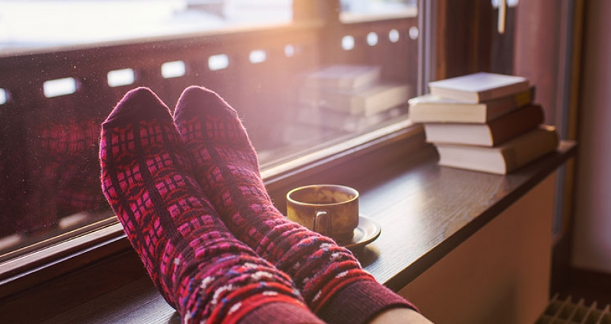 Feet in woollen socks by the Alps mountains view. Woman relaxes by mountain view with a cup of hot drink