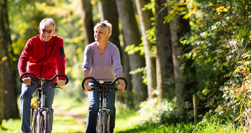 senior male and female riding a bike through a forest path