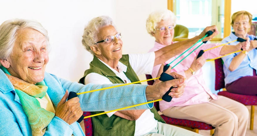 group of older female adults doing stretching exercises while sitting down