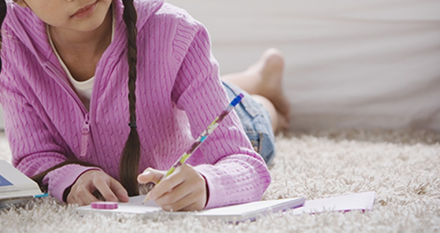 close up of girl writing on a notebook