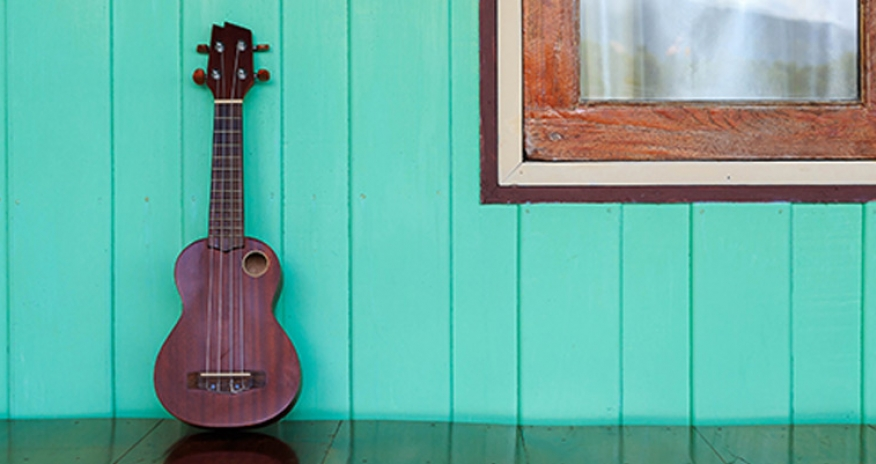 photo of a ukulele against a wall